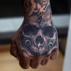 Amazing realistic black and grey skull tattooed on a hand.