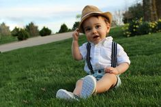 First birthday photo shoot with suspenders, toms, and fedora hat outside spring