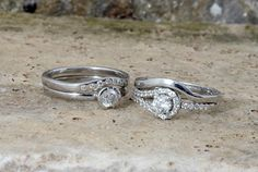 Two pairs of engagement rings and wedding rings shaped perfectly to match one another.