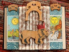 "Altered Books: ""The King of the Beasts""  recycled book, tarot cards, wooden toy lion, wooden musical instrument parts, Japanese paper, rubber stamp and ink, and gel medium"