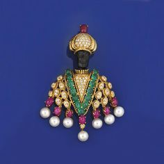 A gemset blackamoor brooch The onyx head to brilliant-cut diamond detailed turban with cabochon ruby accent, the brilliant-cut diamond torso with central cabochon emerald 'v' shape decoration, suspending a tassle fringe composed of single cultured pearl drops with cabochon ruby surmounts, the central drop with brilliant-cut diamond accent