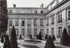The garden of the Hotel Lambert with its resident standing in the open window.
