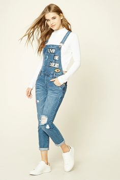 "A pair of overalls featuring a ""Livin The Dream"" graphic, six-pocket construction, tiger and eye patches, a distressed design, adjustable straps, slide-lock closure, and button sides."