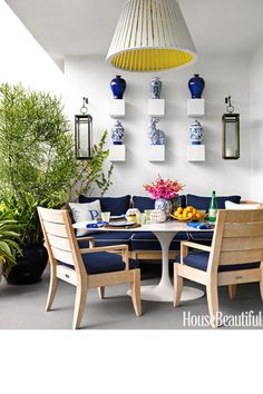 The outdoor dining area of designer Robert Passal's Miami Beach apartment is sheltered from the sun and furnished with comfortable chairs and a sofa, all from the Santa Barbara collection by Restoration Hardware. A Saarinen table by Knoll adds a modern touch. Hanging fixture from Vagabond Vintage.