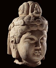 A stone head of a Bodhisattva. The stone head represents the head of a Bodhisattva. The hair is decorated with the image of Buddha. The full lips and the deep carved eyes looking downward convey the love and compassion of a Bodhisattva for mortals. China, Tang Dynasty (618-907 A.D.) artfinding.com