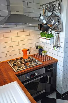 Love the black cupbaords and the orange coffee pot (and the subway tiles, and the wood bench tops ...)