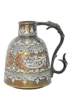 AN ISLAMIC SILVER ANS COPPER INLAID BRASS EWER