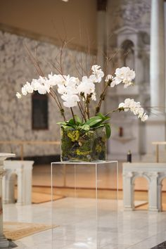 Square Lucite pillars topped with earthy arrangements of phalaenopsis orchids and branches flanked the ceremony altar.