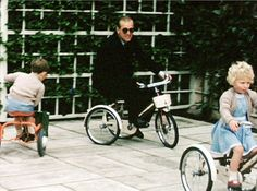 Prince Philip (centre) and Prince Charles (left) appear to be following Princess Anne (right) as they all play on children's tricycles in the royal grounds