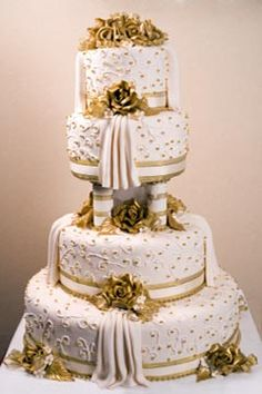 A large four tier white and gold ethnic wedding cake made with buttercream icing and covered over with fondant frosting then decorated with gold embellishments.