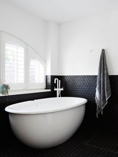 #designmilk #northbourne #architecture #melbourne #modern Photo by Eve Wilson The new master bathroom is outfitted with charcoal Japanese mosaic tiles, which contrast the white paint and fixtures.