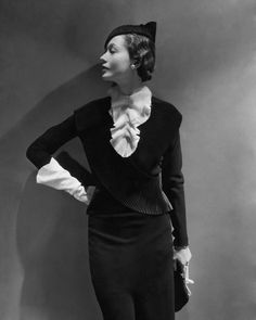 """Toto Koopman - """"All the attention goes to the neck, with a hundred ways to accent its importance. Mainbocher adds a jabot of crinkly pleated white chiffon to a little guimpe that mounds about the throat of a black wool dress, '412,' garnished by a pleated bertha of crinkly black satin ribbon. The black antelope bag is from Germaine Guérin; the Mainbocher hat is of black felt."""""""