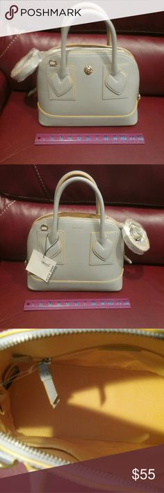 """NWT Anne Klein Grey Satchel Final Price This is a beautiful Lt Grey Small Billie Satchel with strap, detailed in yellow.  Man made materials, zips closed,  inside there is a small zippered section on one side and 2 pockets on the other.   It measures about 11.5"""" long, 9.5"""" high, and 4.5"""" deep.   This is a final price item but you can still save 15% when you bundle. Anne Klein Bags Satchels"""
