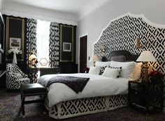 Diane Von Furstenberg design. supersized headboard matching the bedskirt / unity between wall & furniture pieces