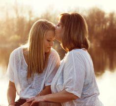 Foto de madre e hija a la orilla de un lago al atardecer