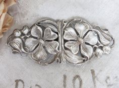 This is a gorgeous large antique French silver plated Art Nouveau buckle dating to the early 1900s.  Just beautifully made and so pretty, it is decorated with large open clematis flowers with flowing leaves and flower buds. It would have been attached to a pretty cloth belt and would have been the finishing touch on an elegant ladys outfit.  Ready to be used again, it just needs a pretty fabric belt to be added to it and once again would make a wonderful addition to a vintage inspired…