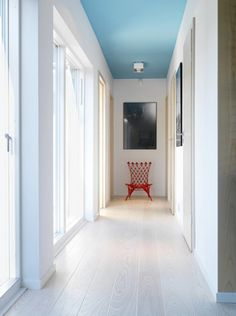 I adore the red pulling you towards the end of the clean white and blue hall- Sara Sjögren