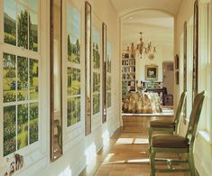 ...a series of trompe l'oeil windows depicting the residences of family and friends. Between each painted window is a long antique mirror to bring even more light into the space. And the door at the end of the hall was removed and replaced by an open arched doorway.