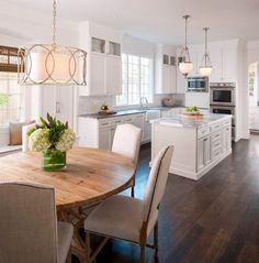 Amidst all that white cabinetry and shiny surfaces, the dark hardwood tones of the floor and the lighter, honeyed warm tones of the breakfast table and blinds give this kitchen area a nice ,welcoming feel.