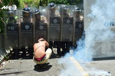 A student from the Central University of Venezuela protects himself during clashes with riot police in a protest against Venezuelan Government in Caracas on May 4, 2017. Anti-government protests raged...