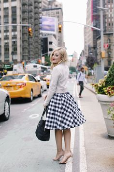 Neutral cardigan, black and white gingham midi skirt, nude strappy heels, and black handbag