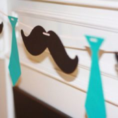 "Instead of the ties, use navy bowties. Keep the mustaches. Follow this sequence, ""Mustache, Bowtie, It's A Boy (Letters), Mustache, Bowtie."" Punch holes through letters/mustache/bowtie and slip through twine and hang!"