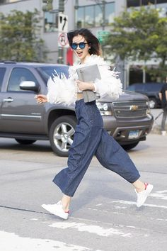 Irene Kim in ankle skimming denim and a feathered bolero. #NYFW #Offduty