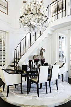 A dramatic staircase is taken to the next level with a black-and-white color scheme and an over-the-top chandelier.   - HarpersBAZAAR.com