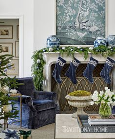 Four blue velvet stockings hang from the composite-stone mantel, which is draped with cedar garlands and adorned with blue and silver balls. - Photo: Emily Jenkins Followill / Design: Amy Morris