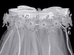White Veil features organza flowers with crystals and pearls is beautiful to complete any First Communion dress. Veil measures approximately 24 inches.