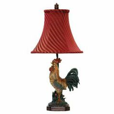 "Table lamp with a rooster base and striped bell shade.  Product: Table lamp    Construction Material: Metal, fabric and composite wood     Color: Red and multi   Features:  Rooster design    Bell shadeStripe accents   Accommodates: (1) 60 Watt  medium base bulb - not included   Dimensions: 24.25"" H x 11.5"" Diameter"