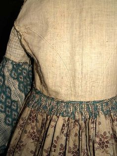 """1850s teal stripe challis dress. Deaccessioned from NY Museum.  Mostly hand sewn.  Pagoda sleeves trimmed in matching green ribbon and double ruching around armsycyes.  Piped at neck, waist & armcyes, bodice has original concealed hooks & eyes and is fully lined with cream linen & window pane linen, cartridge pleating on skirt, hem edged with green hem protector, right side pocket on skirt, skirt lined with floral calico.  Bust: 32""""; Waist: 28""""; shoulders across: 17""""; total length: 57"""" in…"""