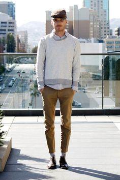 Shop this look on Lookastic:  http://lookastic.com/men/looks/flat-cap-crew-neck-sweater-longsleeve-shirt-chinos-derby-shoes-socks/5353  — Brown Flat Cap  — Grey Crew-neck Sweater  — Grey Long Sleeve Shirt  — Brown Chinos  — Dark Brown Leather Derby Shoes  — Grey Socks