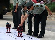 中国・北京(Beijing)にある装甲兵工程学院(Armoured Forces Engineering Academy)で、披露された踊るロボットと微調整を行う人民解放軍(People's Liberation Army、PLA)の士官候補生たち(2014年7月22日撮影)。(c)AFP/Greg BAKER ▼24Jul2014AFP|中国人民解放軍、踊るロボットを公開 http://www.afpbb.com/articles/-/3021293