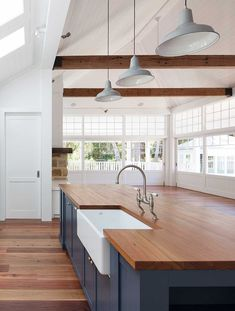 Farmhouse sink in modern styled kitchen with exposed beams. Nice blend of style