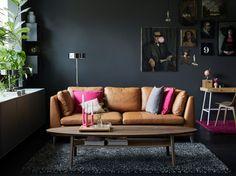 Naturfarget skinnsofa med rosa og grå puter i ei stue med mørkegrå vegger.