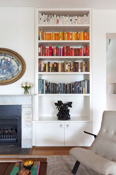 a book rainbow on the corner shelves in living room