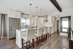 Wite kitchen with white leather bar stools and mini glass pendant. Kitchen with mini glass pendant lights over white kitchen island with granite countertops