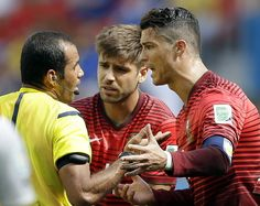 Portugal's Cristiano Ronaldo, right, and Miguel Veloso crowd around referee Nawaf Shukrallah of Bahrain during the group G World Cup soccer ...