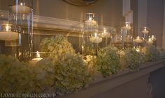 Romantic candle light and hydrangea on a fireplace mantle for a ceremony.