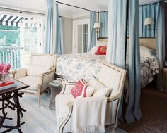 Tempting Terrace- A pair of armchairs at the foot of a canopy bed outfitted with blue curtains  (Source: Lonny)