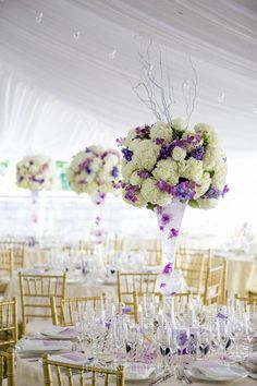 These tall and gorgeous purple and white centerpieces were the perfect romantic touch for this tented wedding reception we designed, For more wedding inspiration, visit our website right now! #englishgardenparty #outdoorwedding