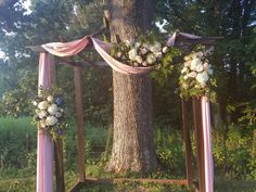 Dark brown pergola with fabric and florals