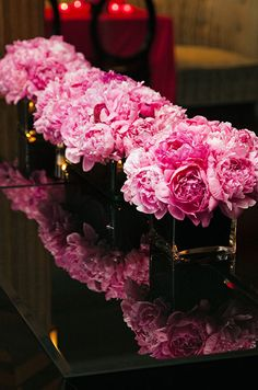 Pink peonies stand out among the dark décor that surrounds-fabulous for a reception lounge!