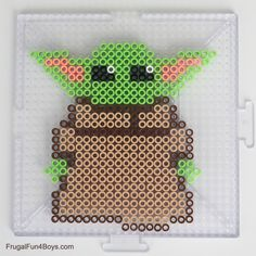 Make your own adorable Baby Yoda out of Perler Beads! This is a fun craft for any Star Wars fan. We've also got a Mandalorian helmet pattern to make. Who is Baby Yoda? If you're not familiar with… Perler Bead Designs, Perler Bead Templates, Hama Beads Design, Melty Bead Patterns, Pearler Bead Patterns, Perler Patterns, Beading Patterns, Loom Patterns, Melty Beads Ideas