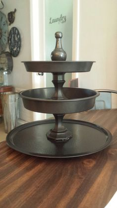 Three tier display stand. Created from dollar tree items, pizza pan, 2 cake pans, 2 candle sticks and a curtain rod finial to top it off. Finally, painted with rust Oleum's hammered black spray paint. I love it, 7.00 in items plus the cost of paint!!!
