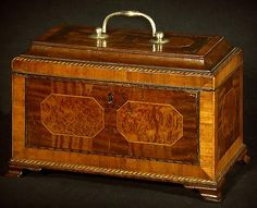 A Fine George III Mahogany Tea Caddy -   CIRCA 1790 - Inlaid with burr walnut octagonal panels, mahogany crossbanding and checkerband inlay throughout; the silver mounted lid opening to reveal two ebonised starbursts above a sycamore tambour compartment flanked by two satinwood compartments.