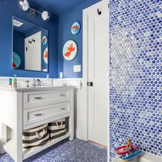 """""""Many of the room designs in the house are inspired by my paintings, as I really wanted to bring their joy into our home"""", this renovator shares in her beach house renovation. Take a look at this goldfish bathroom, covered with blue penny tile and fun goldfish paintings! Bathroom Renovations, Home Renovation, Bathrooms, Blue Penny Tile, Garage Room, Ceiling Murals, Shower Fixtures, Colored Ceiling, Style Deco"""