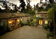 Designer Penelope Bianchi's Provenal farmhouse in Santa Barbara, vines, gravel courtyard, deep inset entry door and hip roof over porch