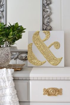 {DIY ampersand art using thumbtacks}